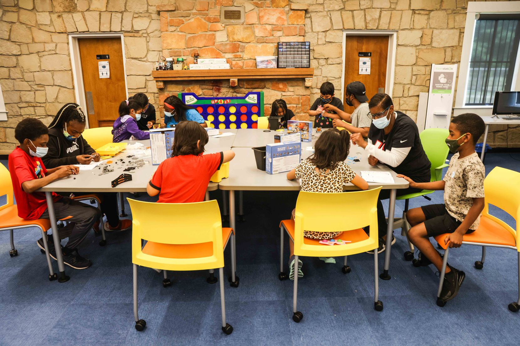 Kids work in groups on Solar Robot Creation Kits as part of the Children's Technology Program at the Juanita J. Craft Recreation Center Annex in Dallas on Thursday, June 10, 2021. (Lola Gomez/The Dallas Morning News)