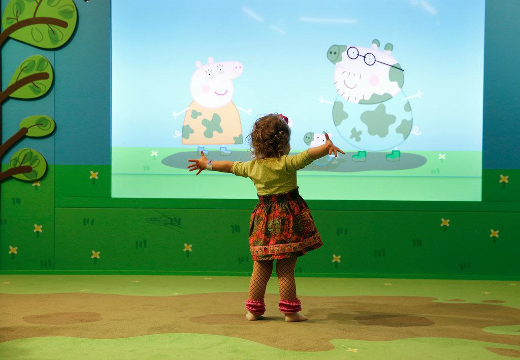 """Standing on a carpet made to look like muddy puddles, Peyton Frazer, 2, of Highland Village, mimics one of Peppa's favorite activities, """"jumping up and down in muddy puddles!"""" Kids seemed enthralled to learn that Peppa, George, Mummy Pig and Daddy Pig would mimic their movements."""