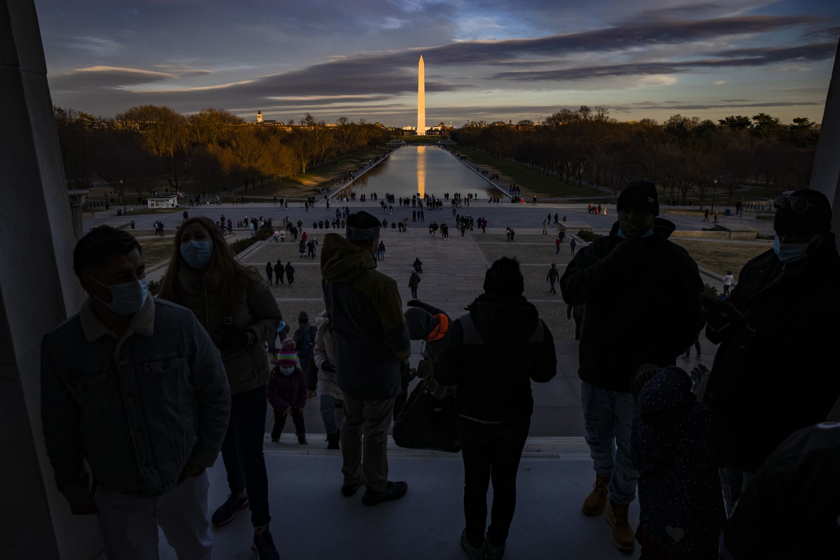 Visitors look out from the Lincoln Memorial across the Reflecting Pool toward the Washington Monument as the sun sets on Saturday, Dec. 26, 2020, in Washington, D.C.