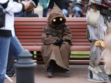 Chay Mullins, 7, dressed as a Jawa, rests on a bench in Celina Square.