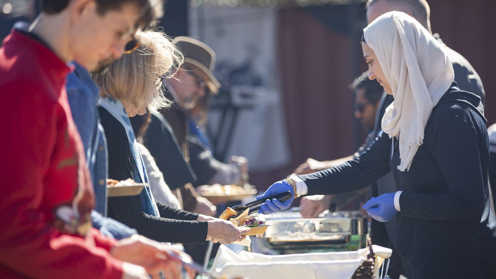 Members of Break Bread, Break Borders serve Iraqi, Syrian dishes and barbecue during an event in partnership with Nasher Prize winner Michael Rakowitz at the F.A.R.M., Farmers Assisting Returning Military, on Feb. 8, 2020 in Dallas. (Juan Figueroa/ The Dallas Morning News)
