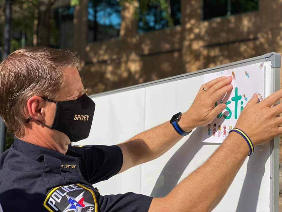 Irving Police Chief Jeff Spivey hangs art in support of George Floyd and the black community.