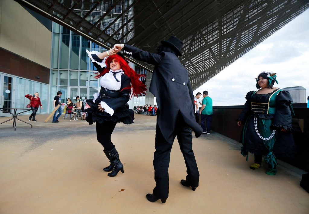 Dressed as character Sebastian Michaelis, Zoey Thornton, right, spins her friend Amanda Dabila, dressed as character Erza Scarlet, as they dance to the music playing outside.