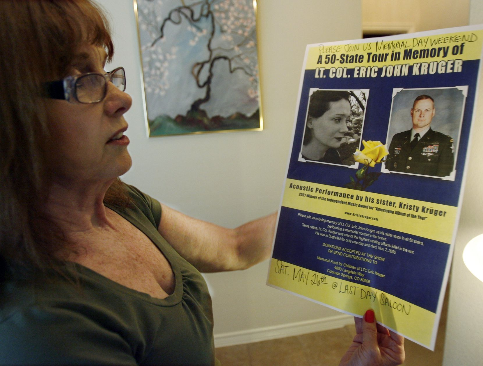 Carol Kruger, mother of Eric and Kristy Kruger, examines a tour flyer about her daughter, who in 2007 planned a tour to honor her late brother after he died while serving with the U.S. Army in Iraq.