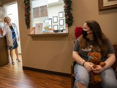 Dr. Lee Pearse waves to Lacie Mitchell, 15, in the waiting room for Dr. Pearse's office on June 25 in Dallas.