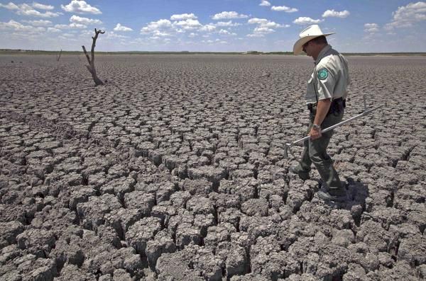 Texas parks officer Thomas Bigham inspected the cracked bed of O.C. Fisher Lake at San Angelo State Park in 2011. Extreme weather from drought to hurricanes is broadly characteristic of a more chaotic climate system.