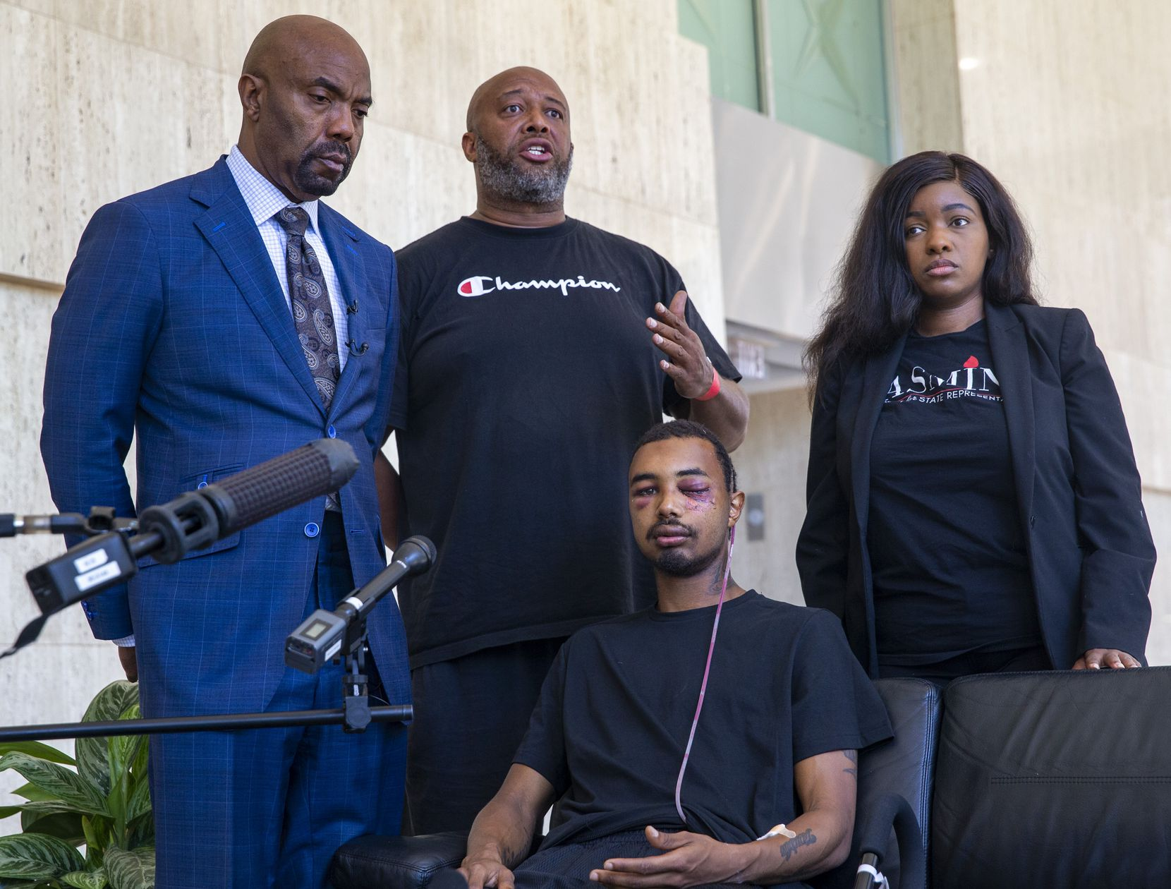 "Andre Ray (center standing) speaks about the severe injuries sustained by his son, Brandon Saenz (center, seated), 26, from a ""less lethal"" bullet fired by Dallas Police at this past weekend's protests during a press conference in downtown Dallas on Wednesday, June 3, 2020. Saenz's lawers are Daryl Washington (left) and Jasmine Crockett."