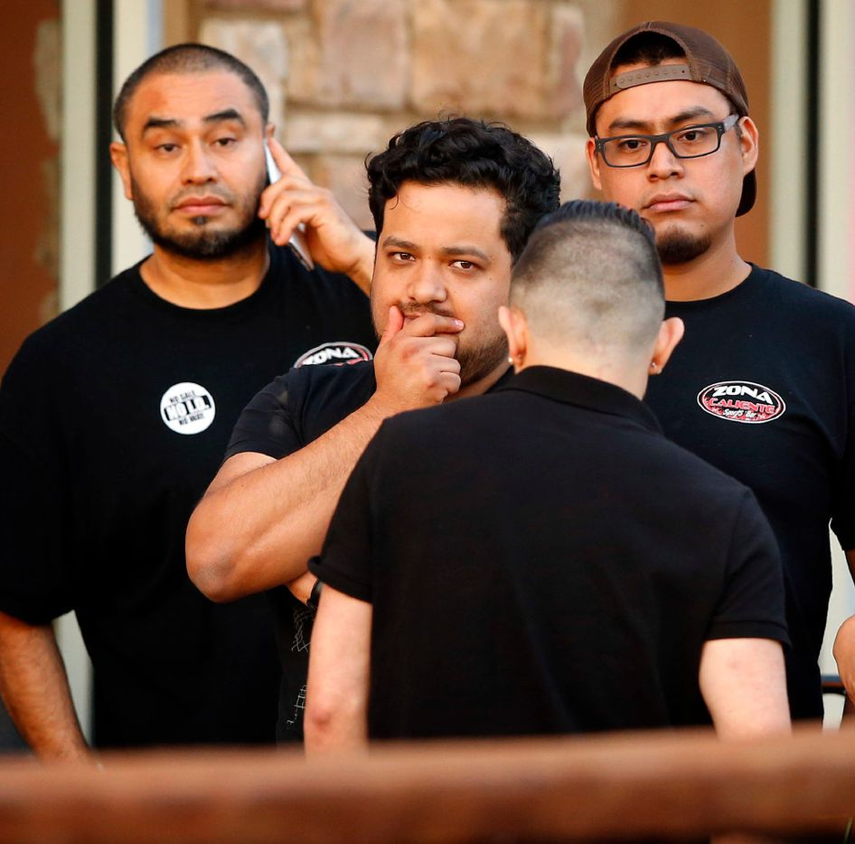 Zona Caliente Sports Bar employees wait outside the restaurant as Arlington police investigate a shooting in which two people were shot dead inside on S. Cooper St. in Arlington, Wednesday, May 3, 2017. The shooting suspect walked to the end of the bar and shot an employee he was talking to. Seeing this happen, a diner got up and shot the suspect dead.  There were 15-20 people at the bar n a handful of employees in the restaurant.
