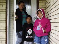 Iris Cañas, junto a sus hijos Gerber y Ximena, en las afueras de su casa en el sureste de Dallas. A la madre salvadoreña no le alcanza para pagar por servicio de internet, lo que ha dificultado la educación de sus hijos durante el encierro debido a la pandemia.