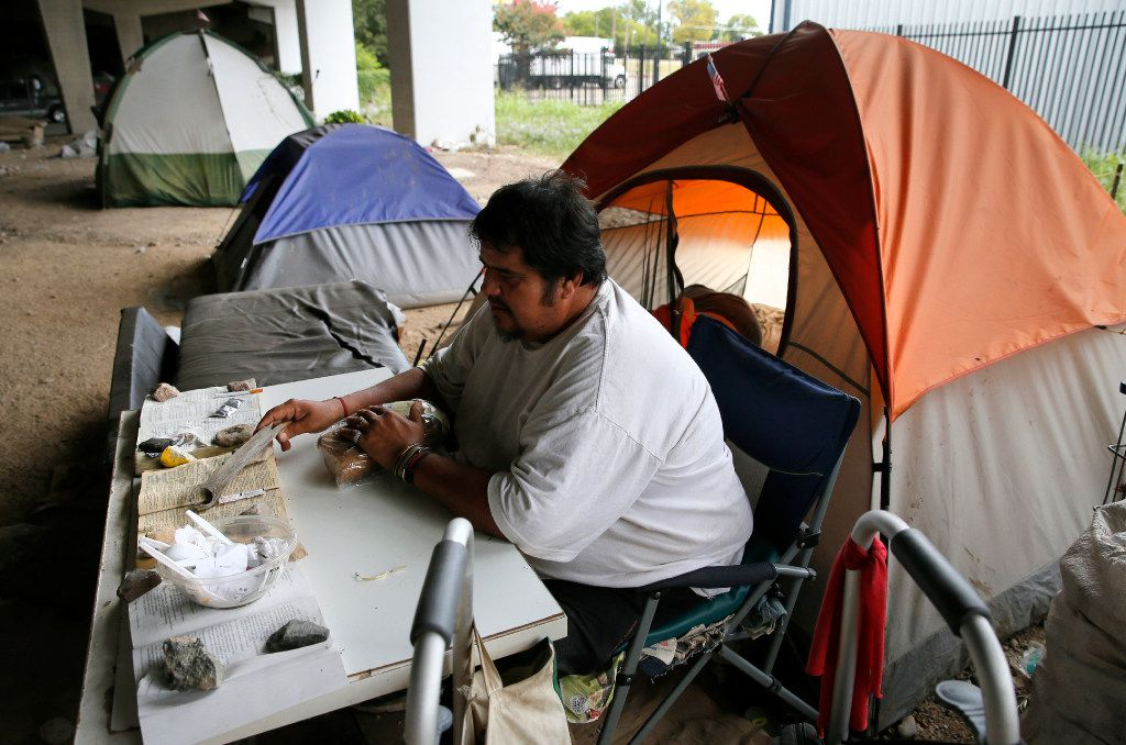 Jose Sanchez read recently while sitting outside his tent next to many others under an Interstate 30 overpass in Dallas.  A collection of tiny homes in Dallas is a sign that Texas is embracing a national trend of giving the homeless permanent housing and augmenting it with plenty of support services. Dallas officials this month unveiled the first of what's expected to be 50 homes that will shelter the city's most chronically homeless.