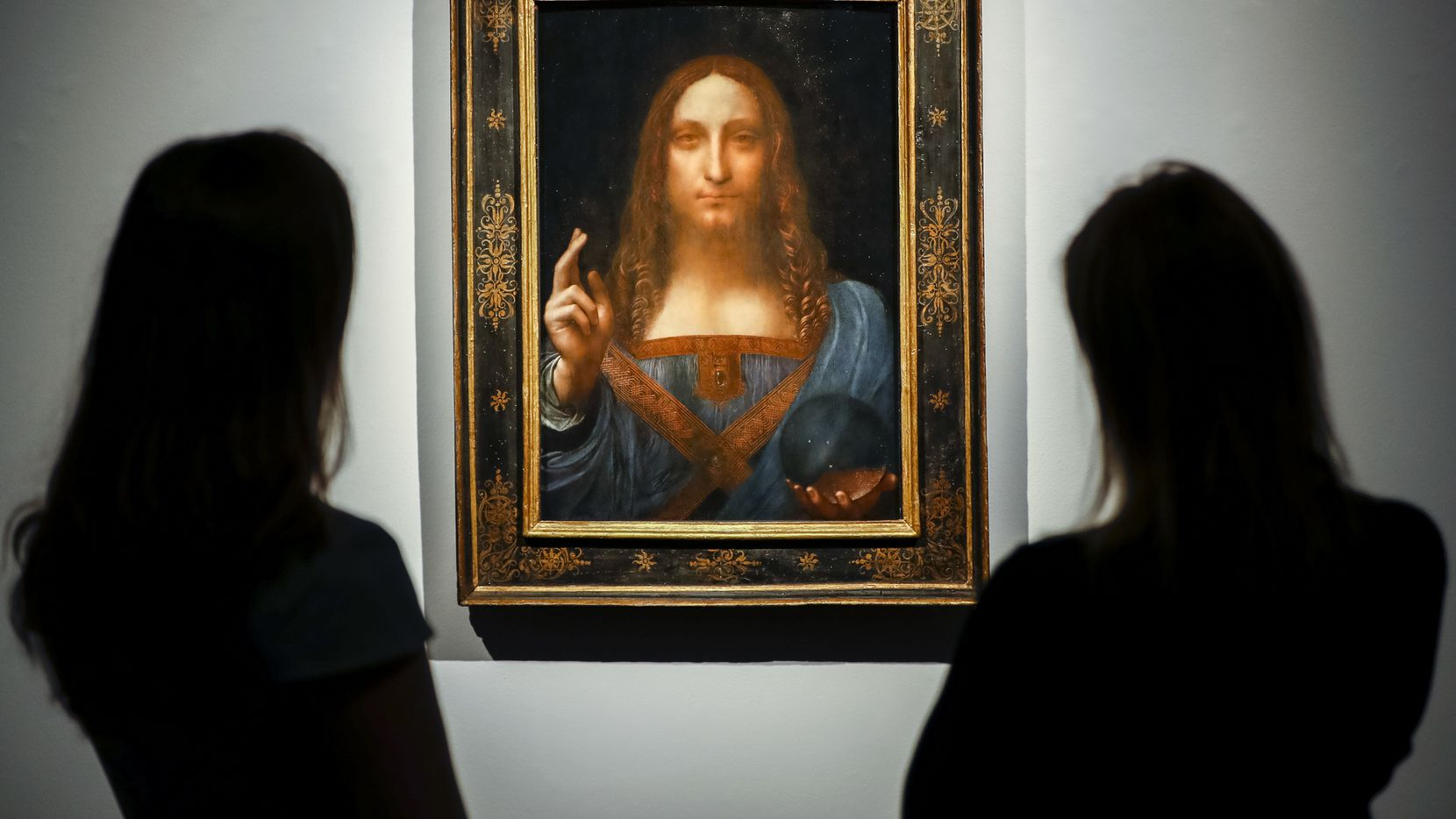 Christie's employees pose in front of Salvator Mundi by Leonardo da Vinci at Christie's auction house in London on Oct. 22, 2017 ahead of its sale at Christie's New York on Nov. 15, 2017.