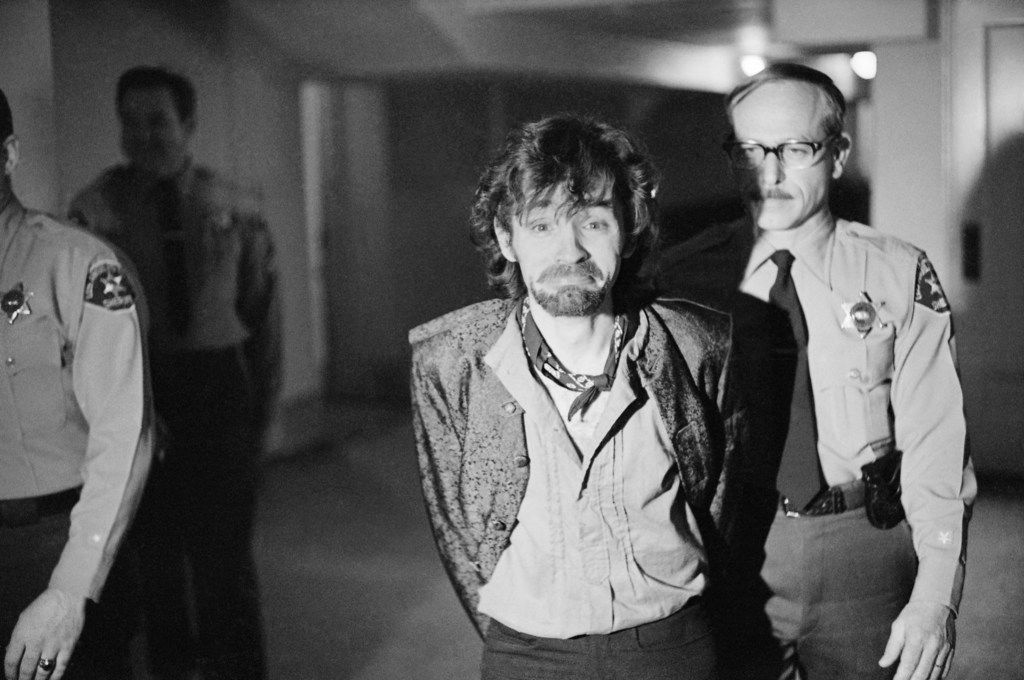 Charles Manson reacts to photographers as he goes to lunch after an outbreak in court that resulted in his ejection, along with three female co-defendants, in the Sharon Tate murder trial.