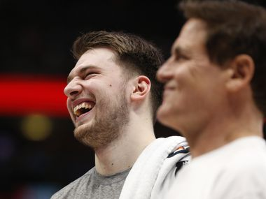 Dallas Mavericks guard Luka Doncic (77) shares a laugh with Dallas Mavericks owner Mark Cuban during the second half of play at American Airlines Center in Dallas on Friday, March 6, 2020.
