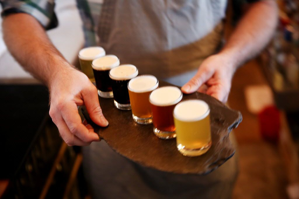 Joshua Dawn, co-owner, delivers a flight of beer to patrons inside Small Brewpub in the Oak Cliff borough of Dallas Saturday September 3, 2016. December 9th will mark the two year anniversary its opening.