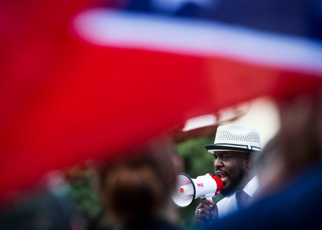 A Confederate flag flies over the shoulder of a counter-protester as Pastor Michael W. Waters speaks during a rally for removal of Dallas' Confederate monuments and public buildings named for Confederate heroes at Pioneer Park Cemetery in Dallas on Thursday, August 10, 2017.