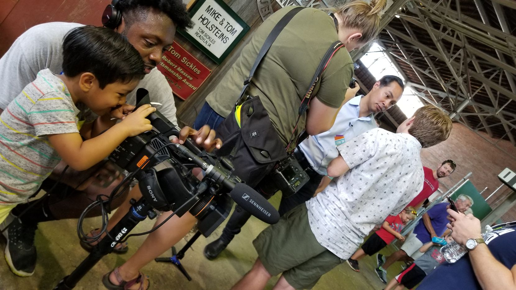 Cristián Castro, 4, peers through a camera with CBS campaign embed Tim Perry as his dad, Julián Castro, stumps at the Iowa State Fair.