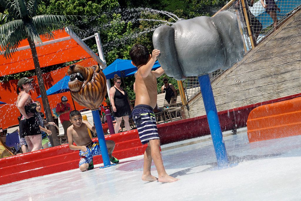 Matthew Esparza (9) and Christian Ross (5) play with the water cannons while visiting Safari Splash Park at the Fort Worth Zoo.