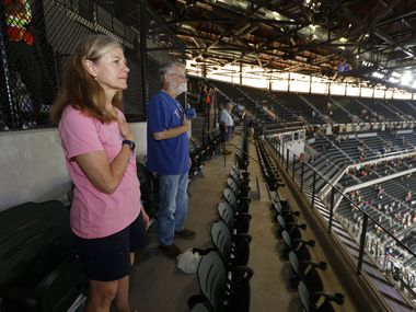 Season ticket holder Pam Lunk of Arlington, and Bob Brewton, of Lewisville, right, stand for the National Anthem prior to an MLB baseball game between the Texas Rangers and the Houston Astros in Arlington, Texas on Thursday, Sept. 16, 2021.