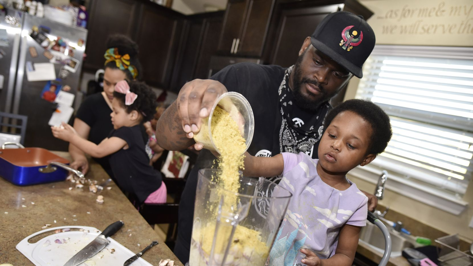 James McGee, shown helping his daughter pour ingredients for a vegan pasta at their DeSoto home in 2019, owns Peace Love & Eatz, a smoothie shop in the city.