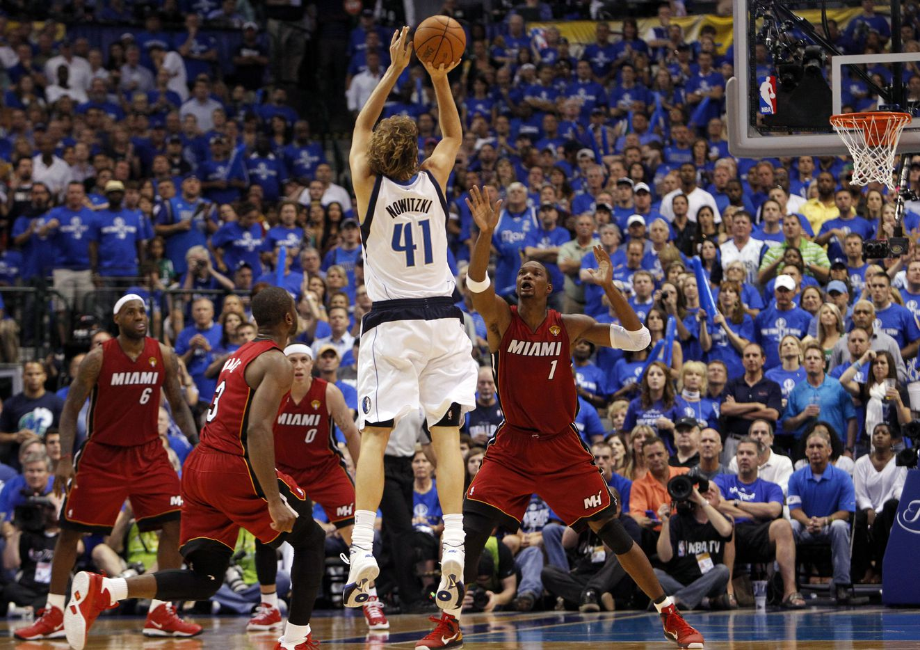 Dallas Mavericks power forward Dirk Nowitzki (41) hits a three pointer against Miami Heat power forward Chris Bosh (1) in the third quarter during Game 3 of the NBA Finals at American Airlines Center Sunday, June 5, 2011 in Dallas.  (Tom Fox/The Dallas Morning News)