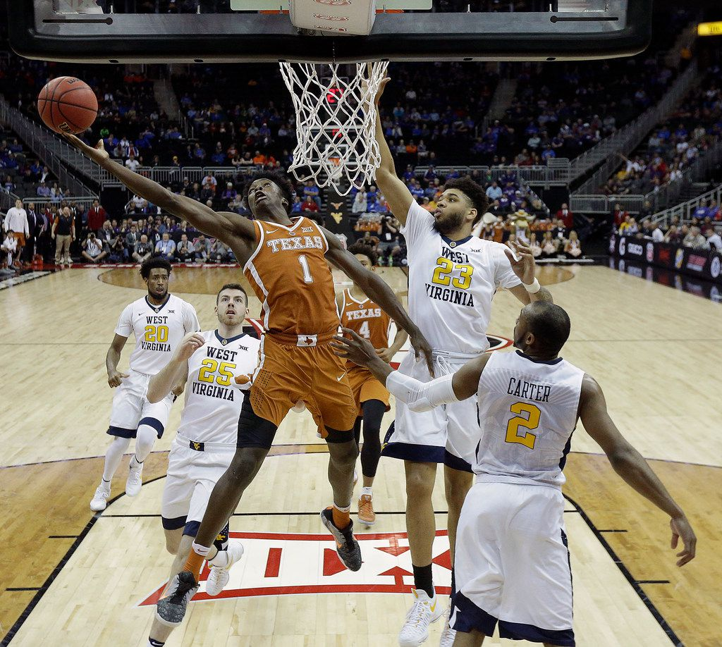 Texas' Andrew Jones (1) gets past West Virginia's Esa Ahmad (23) to shoot during the first half of an NCAA college basketball game in the quarterfinal round of the Big 12 tournament in Kansas City, Mo., Thursday, March 9, 2017. (AP Photo/Charlie Riedel) ORG XMIT: MOCR114