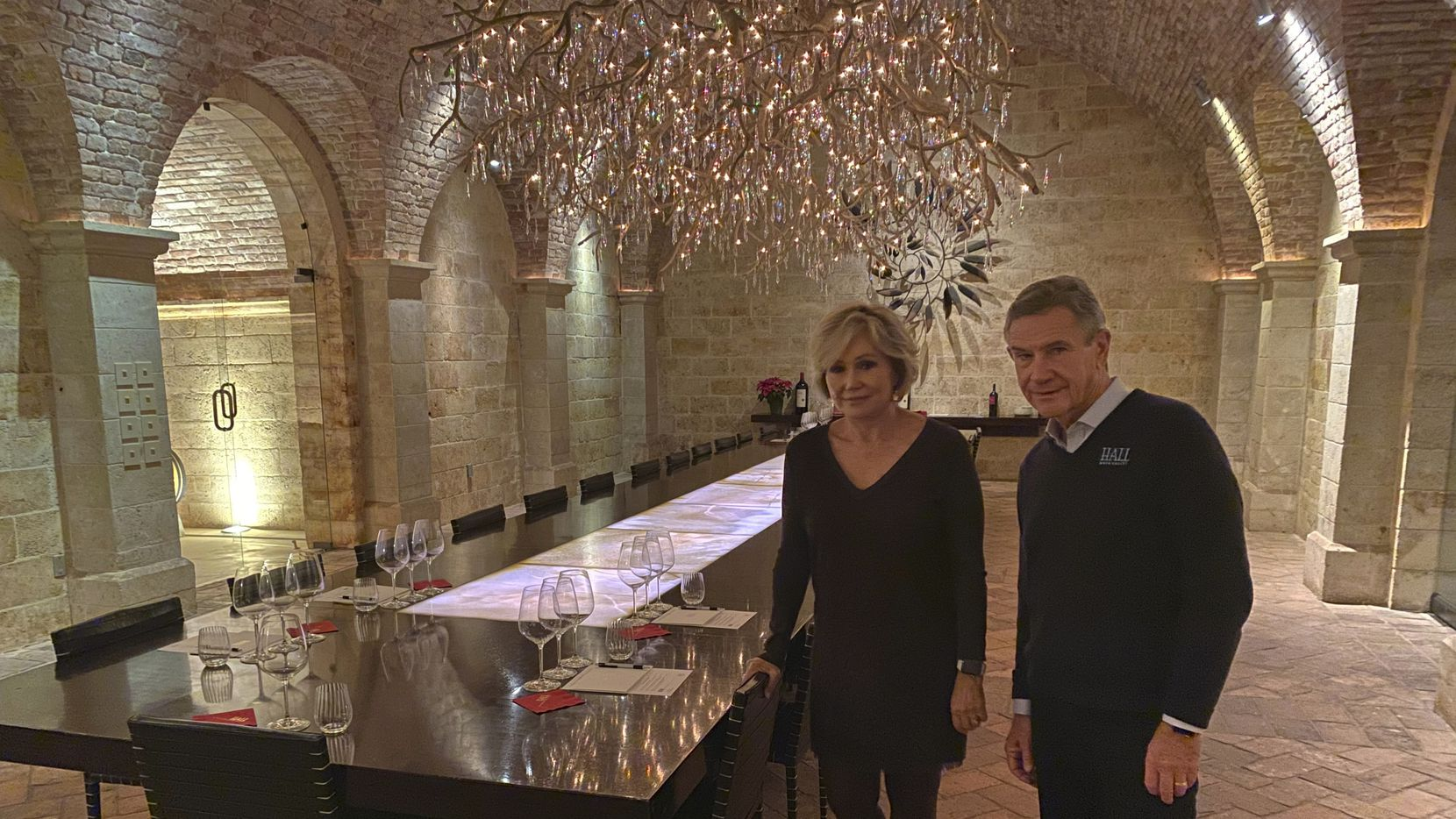 "Kathryn and Craig Hall, owners of Hall Rutherford Winery, stand inside the ""wine cave"" dining room where they held a fundraising dinner for Democratic presidential candidate South Bend, Ind., Mayor Pete Buttigieg, Dec. 20, 2019, in Rutherford, Calif.  They say their most expensive bottle of wine costs $350 and wasn't served at the fundraiser. (AP Photo/Terence Chea)"
