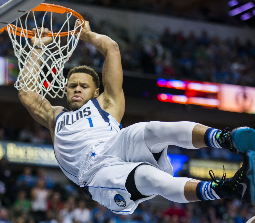 Dallas Mavericks guard Justin Anderson (1) hangs on the rim after dunking the ball during the second quarter of game 4 of their series against the Oklahoma City Thunder in the first round of NBA playoffs on Saturday, April 23, 2016 at the American Airlines Center in Dallas.  (Ashley Landis/The Dallas Morning News)