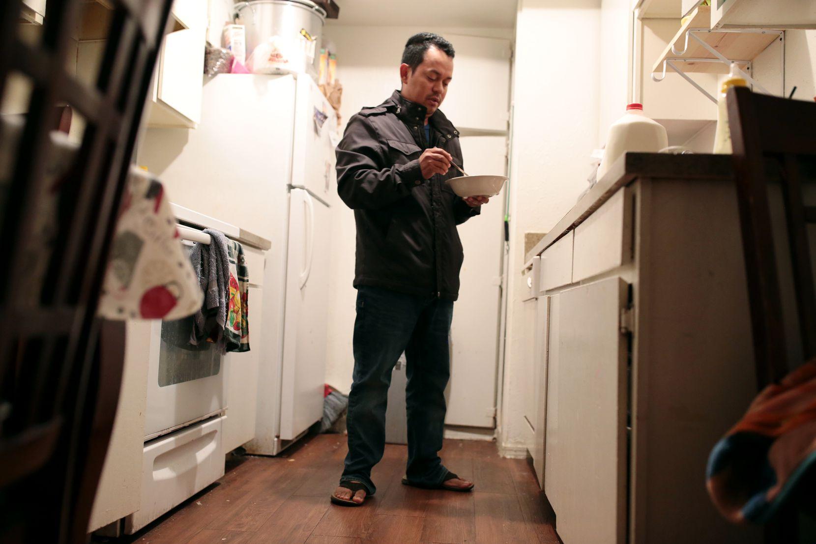 Omar Ortega sostiene el tazón de cereal que le dio a su hijo Michael mientras él se alista para ir a la escuela, el lunes. (ESPECIAL PARA AL DÍA/MARIA R. OLIVAS)