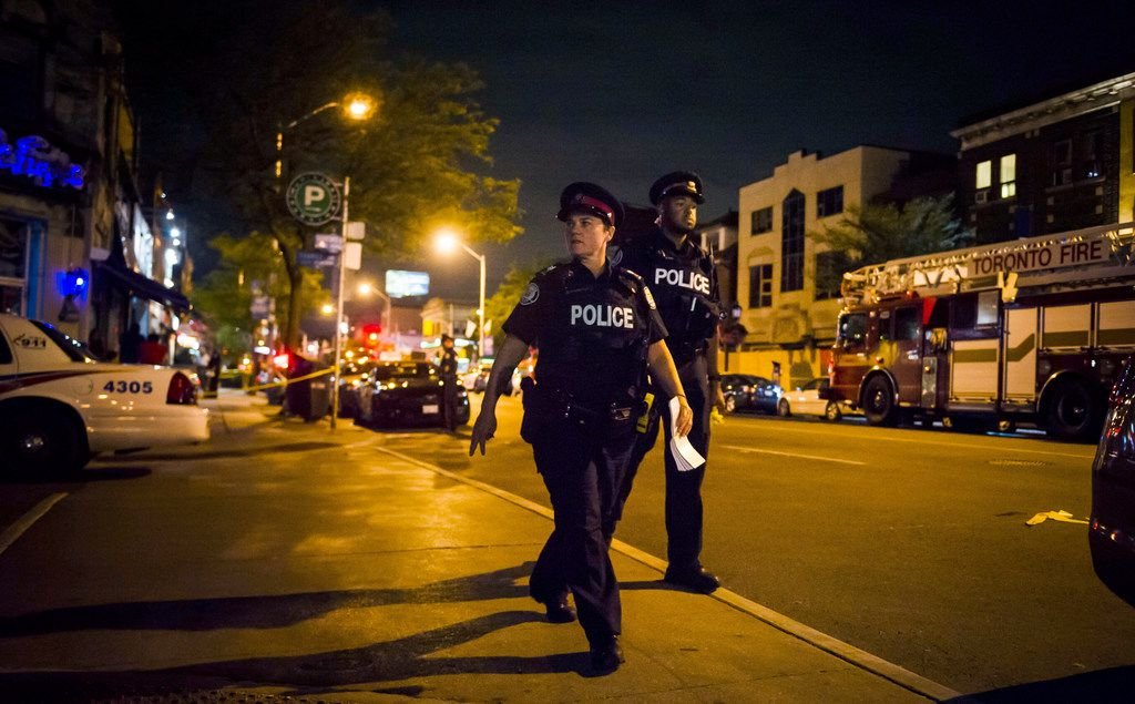 Police secure a perimeter around the scene of a mass shooting in Toronto on Monday.