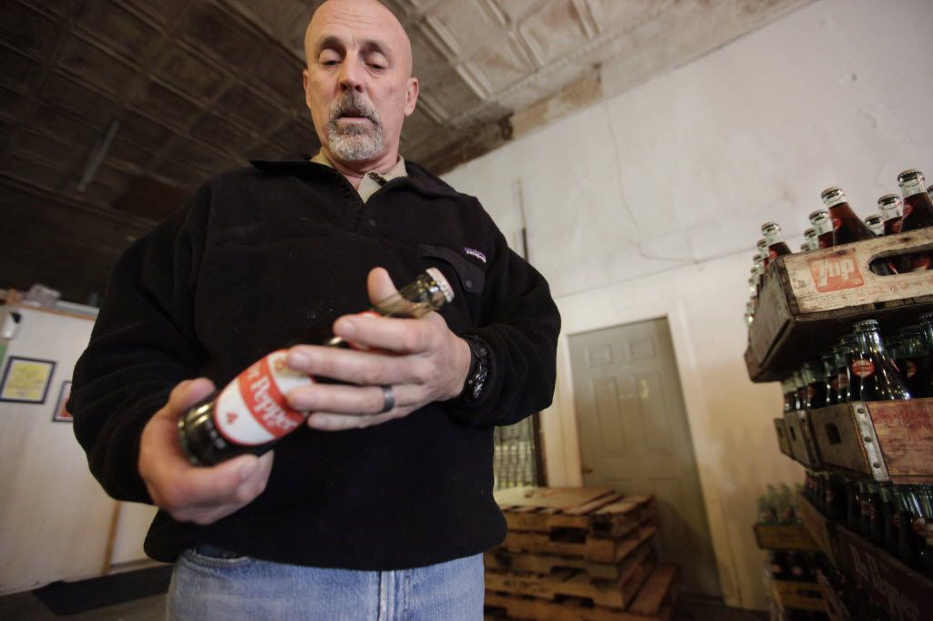 Jeff Kloster, owner of Dublin Bottling Works, looks over one of the last bottles Dr Pepper produced in Dublin during an interview in 2012. Under an agreement with Dr Pepper, the Dublin Dr Pepper bottler will end production of the drink that Kloster's family has been bottling for more than a century.