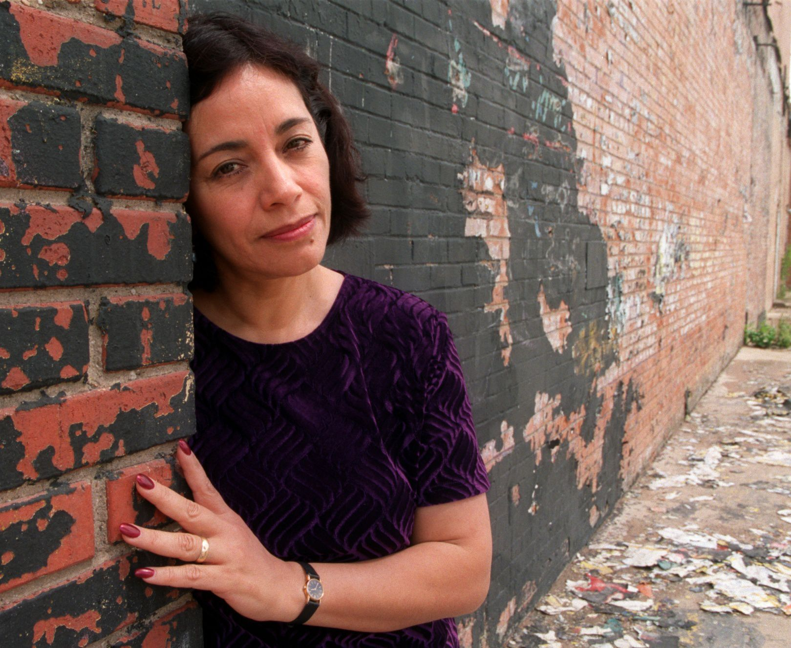 Cora Cardona, co-founder and artistic director of Teatro Dallas, leans on a wall of the company's past location, which was damaged by a fire in November 1998.
