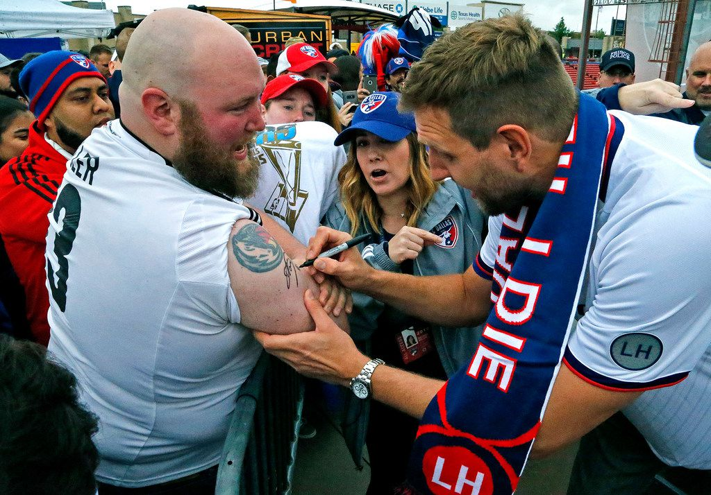 Dirk Nowitzki signs an autograph on the arm of Chase Tripp (left) of Arlington before the start of the game as FC Dallas hosted the New York Red Bulls at Toyota Stadium in Frisco on Saturday, May 11, 2019.  (Stewart F. House/Special Contributor)