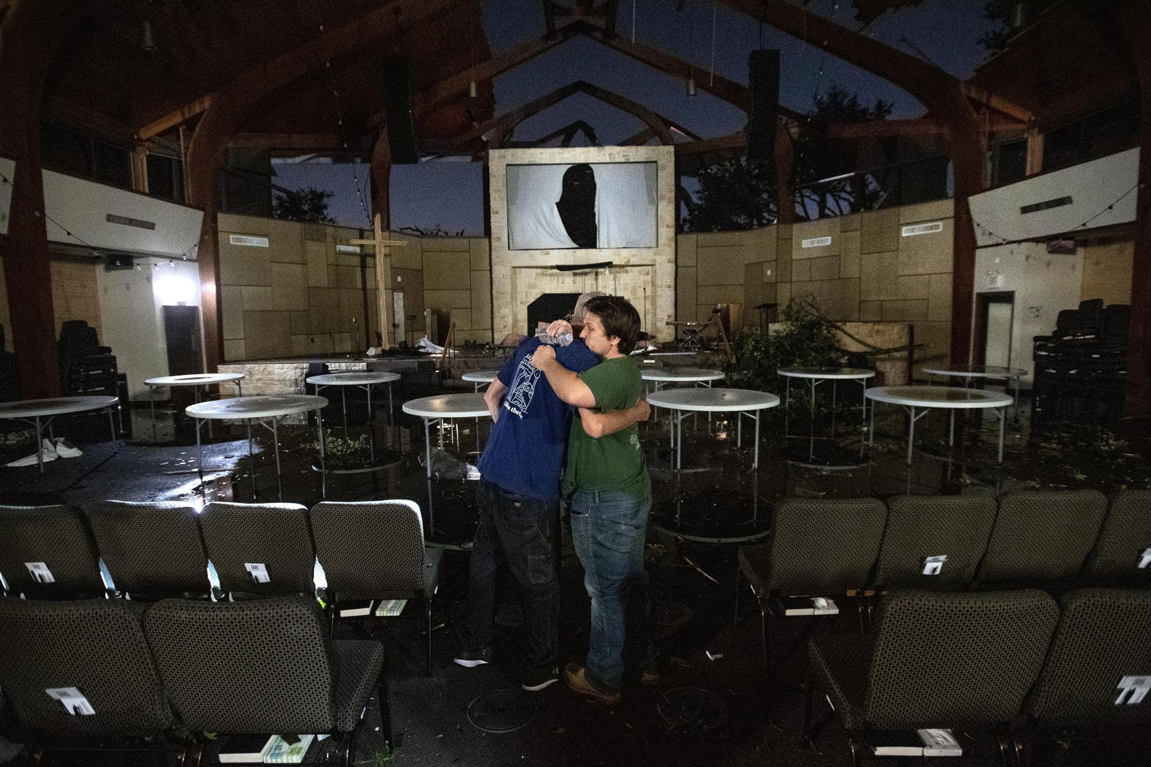 In the moments after the tornado tore through northwest Dallas, Northway Church member Jeffrey McWhorter took this photo of Matt Younger, right, a pastor at Northway Church, embracing facilities associate Robert Lusk in their church's severely damaged sanctuary.