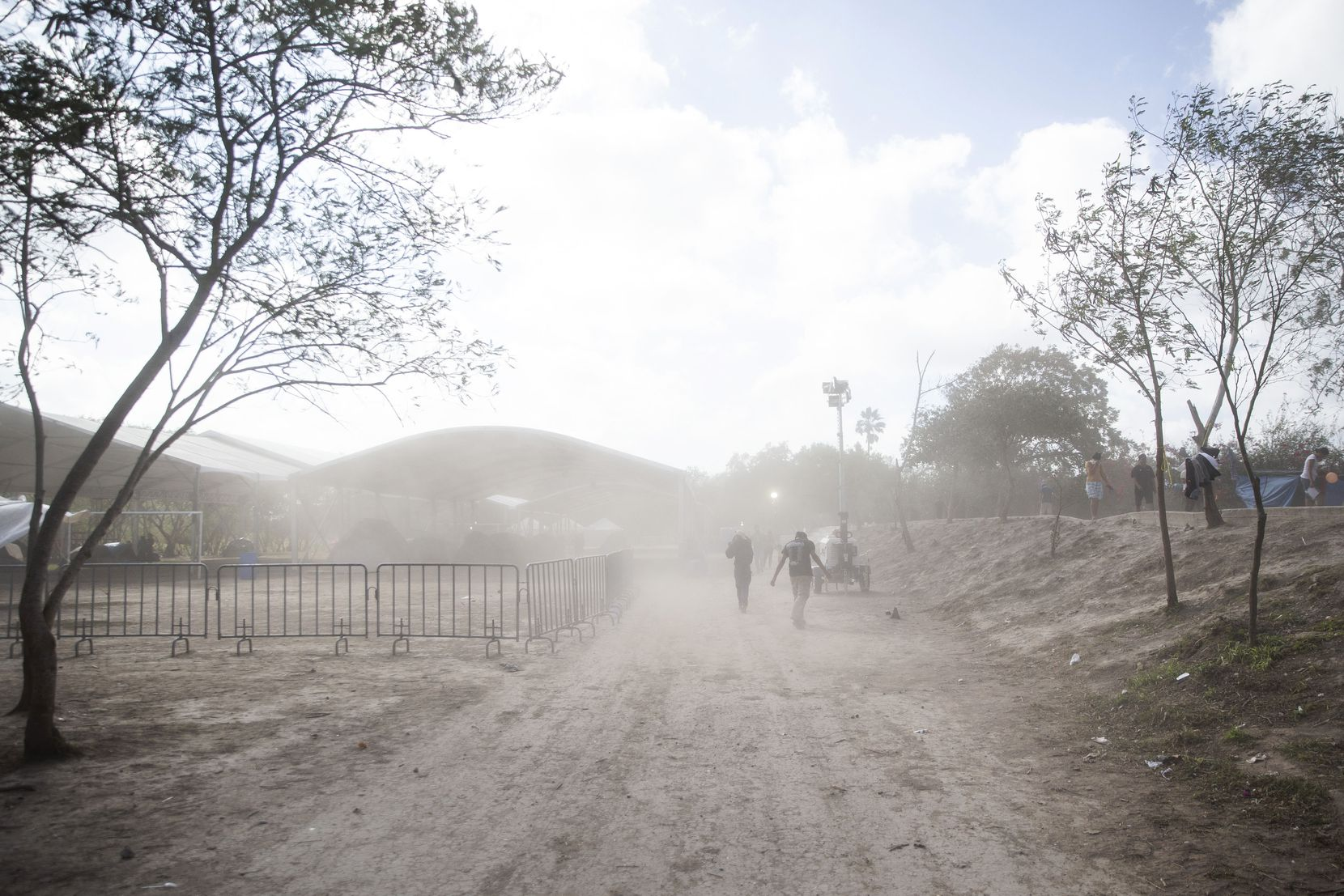 Asylum-seekers walk through a gust of dusty wind in the tent camps in Matamoros, Mexico, on Dec. 15, 2019.  The camp's living conditions have affected the health of residents, medical volunteers said.