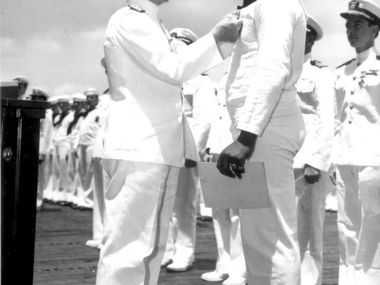"""Admiral Chester Nimitz, the Commander in Chief, Pacific Fleet, pins Navy Cross on Doris """"Dorie"""" Miller, at ceremony on board the USS Enterprise on May 27, 1942."""