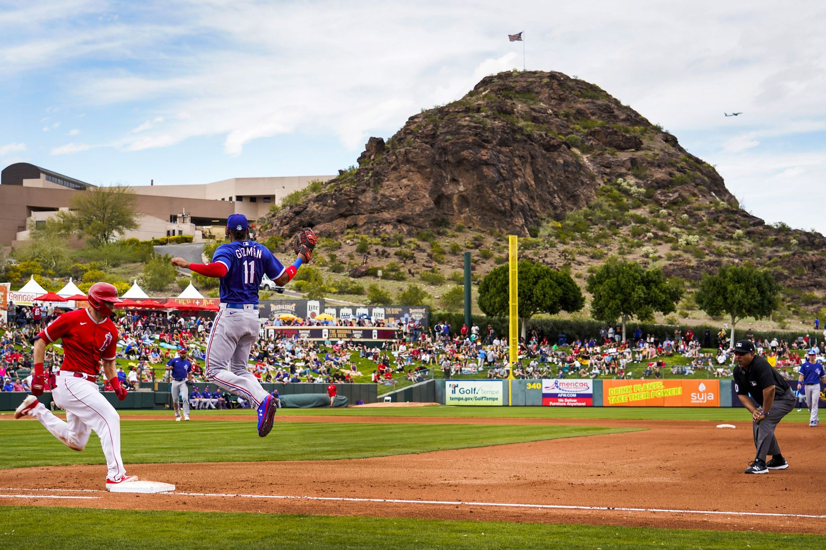 Los Angeles Angels catcher Anthony Bemboom is safe at first on a bunt single as Texas Rangers first baseman Ronald Guzman leaps for the throw from pitcher Joe Palumbo during the fourth inning  of a spring training game at Tempe Diablo Stadium on Friday, Feb. 28, 2020, in Tempe, Ariz.