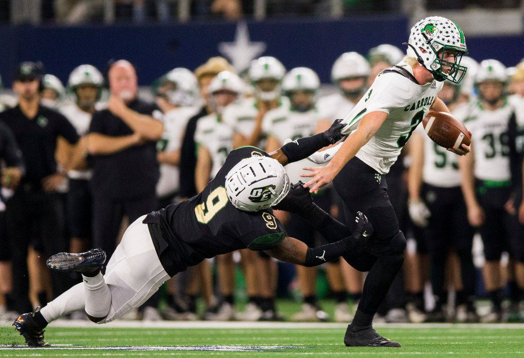 Southlake Carroll quarterback Quinn Ewers (3) is pulled down by DeSoto linebacker Ridarius Branch (9) during the second quarter of a Class 6A Division I area-round high school football playoff game between Southlake Carroll and DeSoto on Friday, November 22, 2019 at AT&T Stadium in Arlington. (Ashley Landis/The Dallas Morning News)