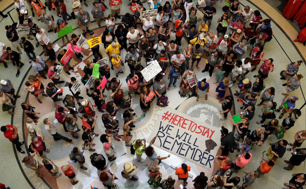 """Protesters gather in the Texas Capitol Rotunda as State lawmakers begin a special legislative session called by Republican Gov. Greg Abbott in Austin, Texas, Tuesday, July 18, 2017. Immigrant rights groups plan to increase protests of the new law that allows police to inquire about peoples' immigration status, while LGBT activists bitterly oppose """"bathroom bill"""" proposals. (AP Photo/Eric Gay)"""