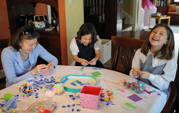Deborah Adams, left, Katherine, 6, center, and Isabelle, 8, create origami ornaments to sell. The money they raise  pays for new water wells in developing countries, where children die from unclean water.