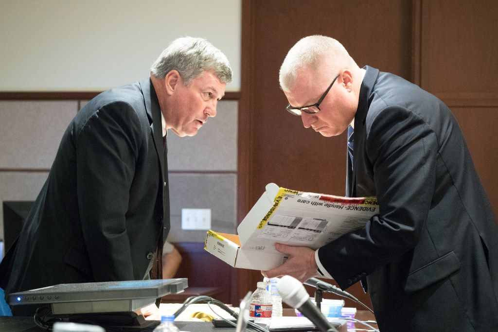 Assistant district attorney Tony Paul presents the gun as evidence to Eric Johnson's attorney, Bruce Isaacks, at the Denton County Courthouse.