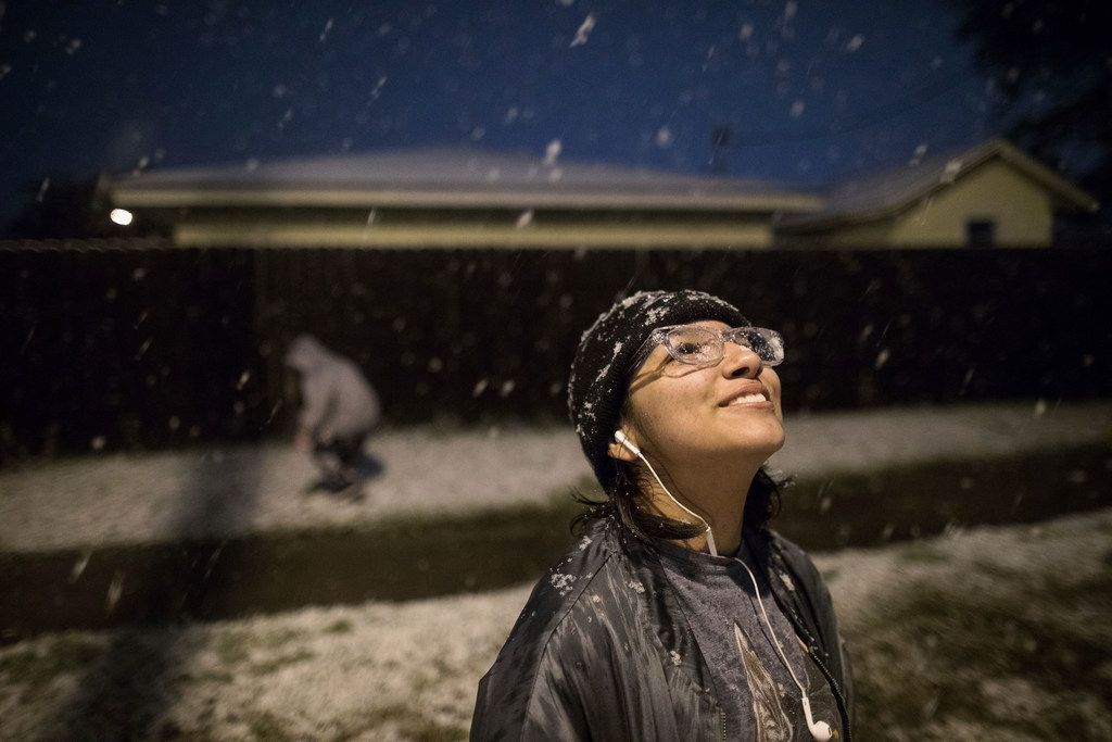 Thirteen-year-old Eva Cantu sees her first snow fall standing on Kostoryz Road looks up to the sky in Corpus Christi on Texas, Friday, Dec. 8,2017.