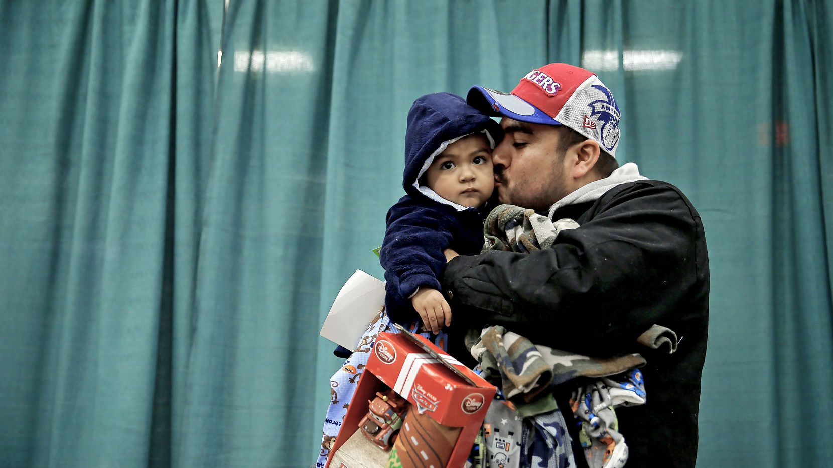 """Jose Gonzalez holds donated gifts as he kisses his son Kareem, 1, during the """"Christmas Gift to the Homeless"""" event in December, 2014 at the Kay Bailey Hutchison Convention Center in Dallas. Operation Care International sponsors the event which provides goods and services to thousands of individuals and families in need."""
