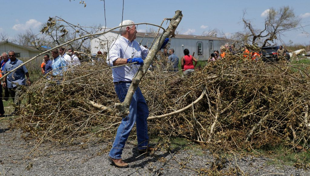 Vice President Mike Pence helps move debris during a visit to an area hit by Hurricane Harvey, Thursday, Aug. 31, 2017, in Rockport, Texas. (AP Photo/Eric Gay)