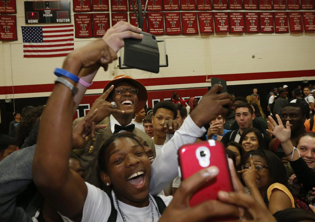 Students swarmed Euless Trinity basketball player Myles Turner, (with orange hat) after he announced his commitment to play for the University of Texas during a ceremony at Euless Trinity in  Euless, Texas, on April 30, 2014. (Michael Ainsworth/The Dallas Morning News)