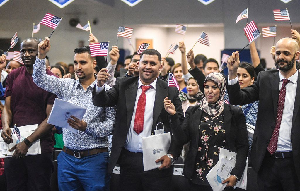 New citizens wave U.S. flags after taking the oath of citizenship during a naturalization ceremony held by the U.S. District Court for the Northern District of Mississippi at Oxford High School in Oxford, Miss., on May 10, 2019. Over 100 people from 44 countries took the oath.
