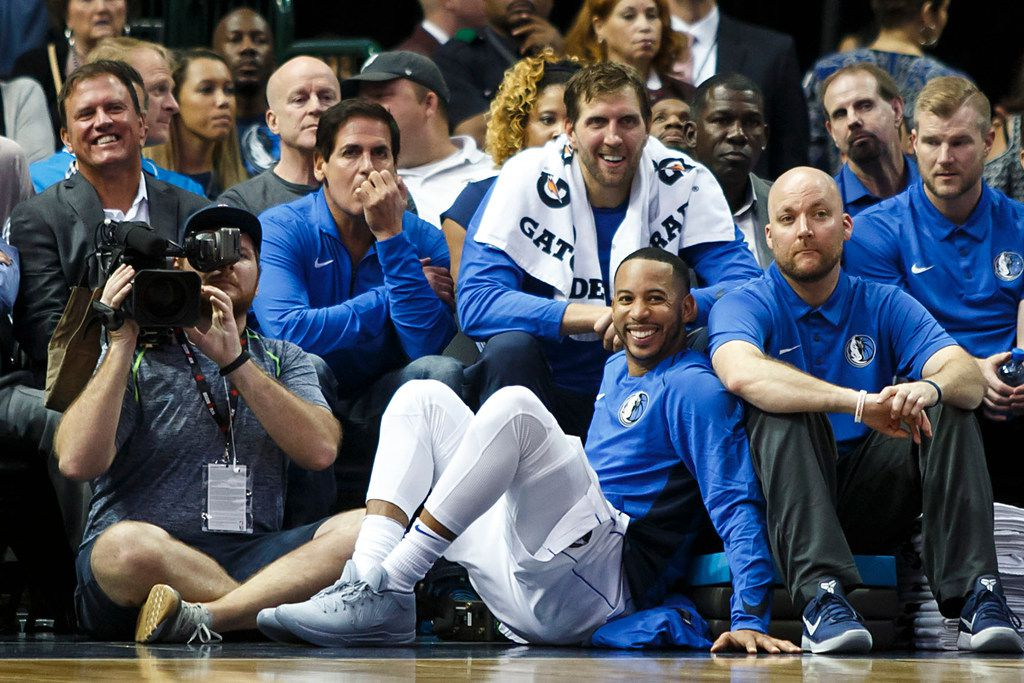 Dallas Mavericks forward Dirk Nowitzki (with towel around his neck) sits in the front row with team owner Mark Cuban and guard Devin Harris (on the floor) as they watch the action during the second half of an NBA preseason basketball game against the Milwaukee Bucks at American Airlines Center on Monday, Oct. 2, 2017, in Dallas. (Smiley N. Pool/The Dallas Morning News)
