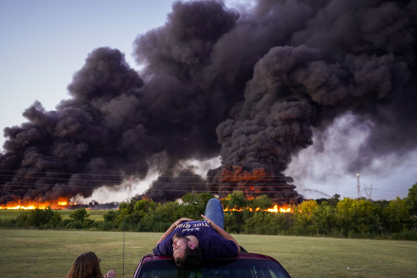 Dakota Stewart sits atop his car in Tyre Park as he watches fire crews battle a massive blaze in an industrial area of Grand Prairie just before sunrise on Wednesday, Aug. 19, 2020.