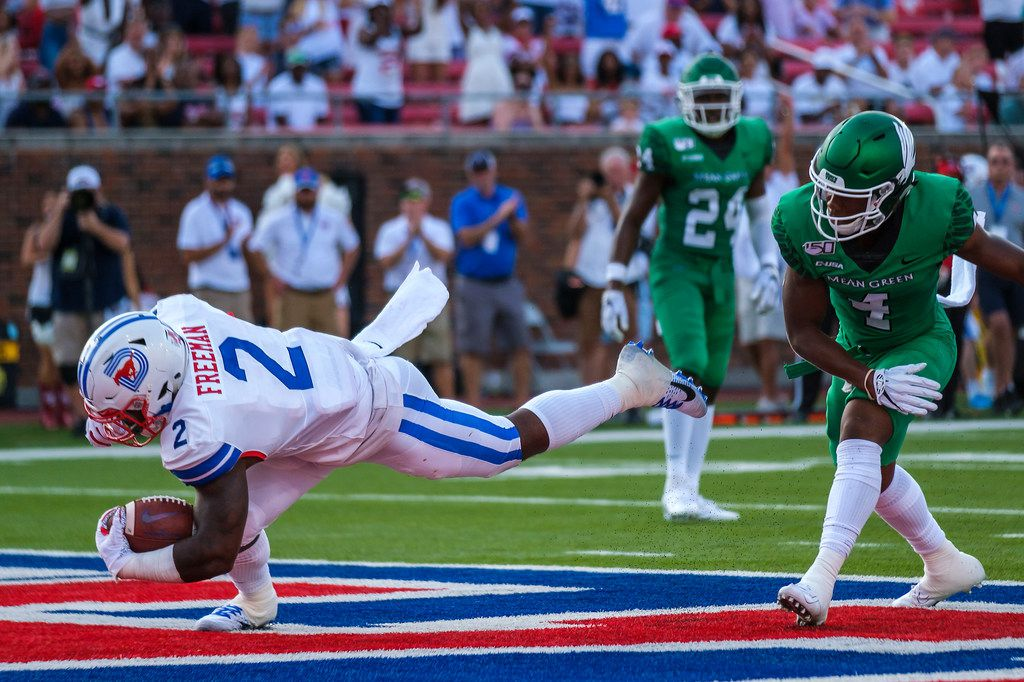 SMU running back Ke'Mon Freeman (2) scores on a 2-yard  touchdown run past UNT safety Khairi Muhammad (4) during the first half of an NCAA football game at Ford Stadium on Saturday, Sept. 7, 2019, in Dallas. (Smiley N. Pool/The Dallas Morning News)
