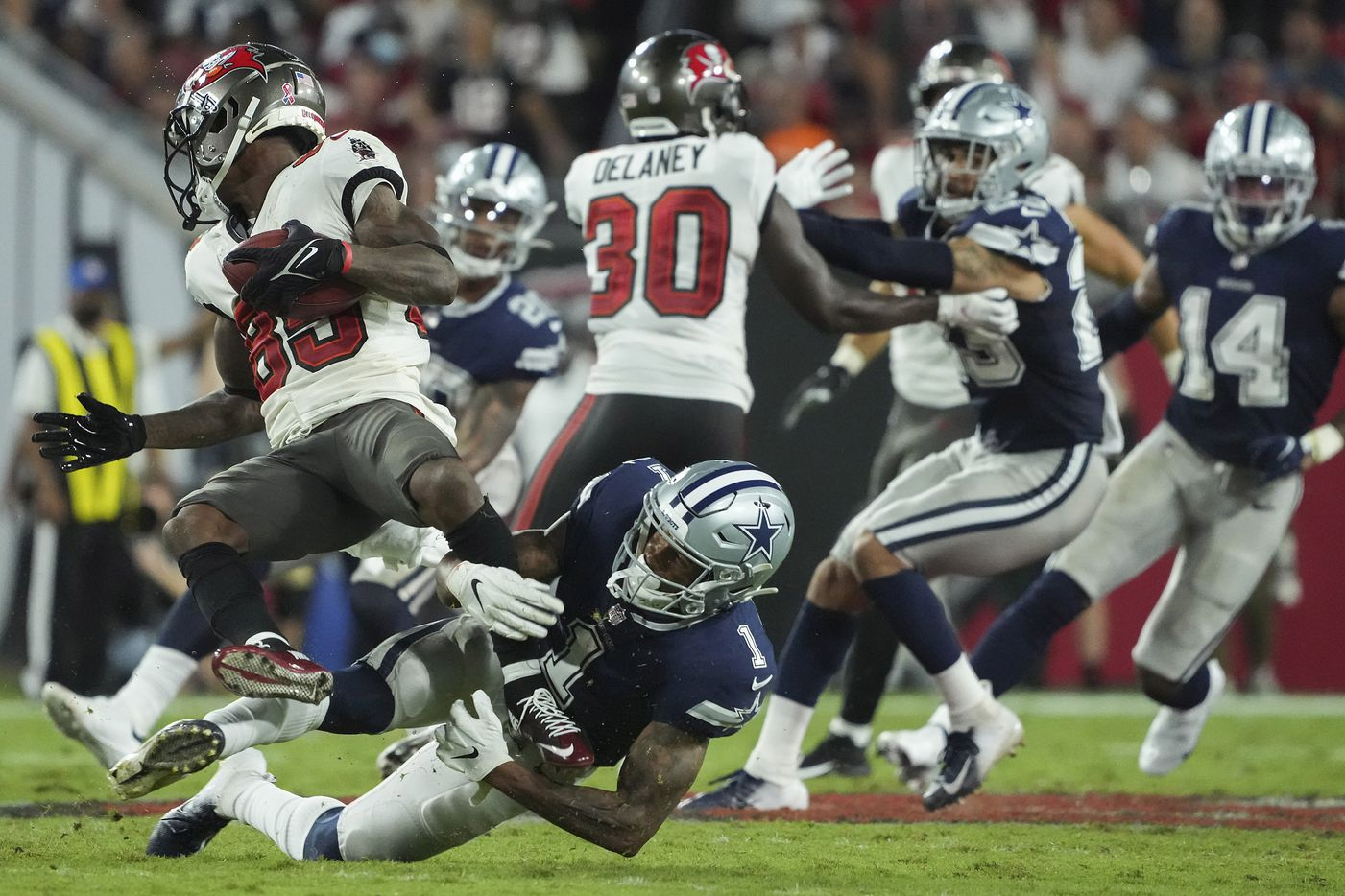 Dallas Cowboys wide receiver Cedrick Wilson (1) brings down Tampa Bay Buccaneers wide receiver Jaydon Mickens (85) on a punt return during the second half of an NFL football game at Raymond James Stadium on Thursday, Sept. 9, 2021, in Tampa, Fla. The  Buccaneers won the game 31-29. (Smiley N. Pool/The Dallas Morning News)