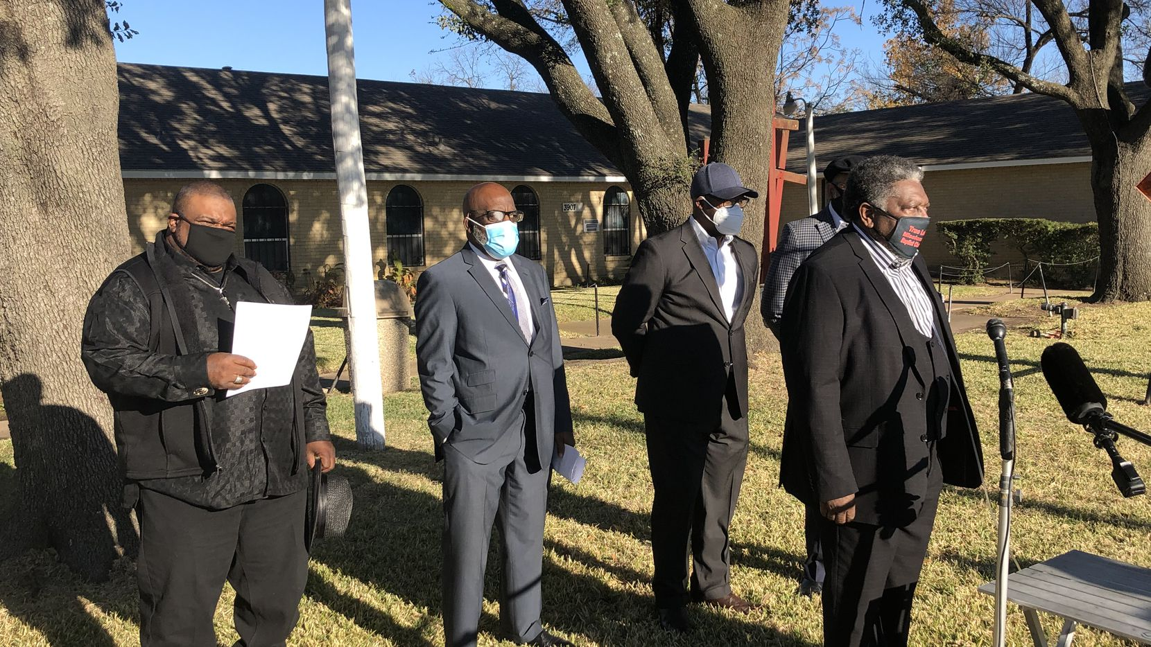 Rev. Donald Parish of True Lee Baptist Church in South Dallas speaks with reporters as fellow pastors line up behind him in December 2020.